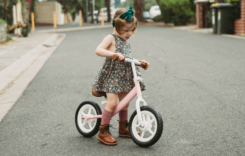 Young girl on a scoot bike.