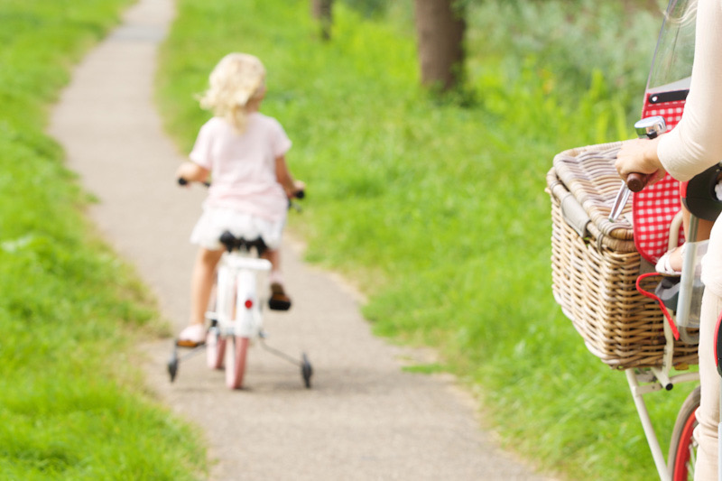 Rear view portrait of woman and little girl riding bikes in park